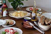 テーブルセッティングされたホットドッグとピクルスとスイカのサラダ